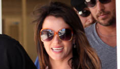 Britney Spears seen wearing engagement type ring; becomes a brunette