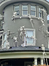 Halloween display featuring skeletons scaling a house