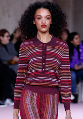 Runway model wearing striped Kate Spade sweater and matching trousers
